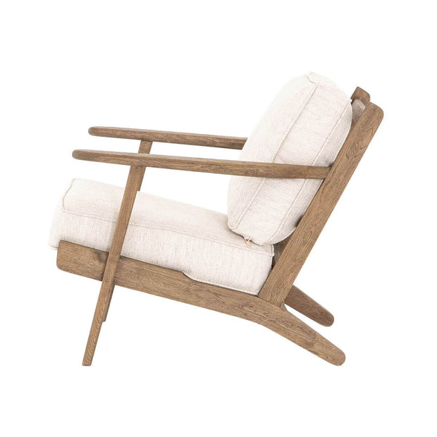 Side view of a modern lounge chair with a solid wood frame and thick, white cushions.