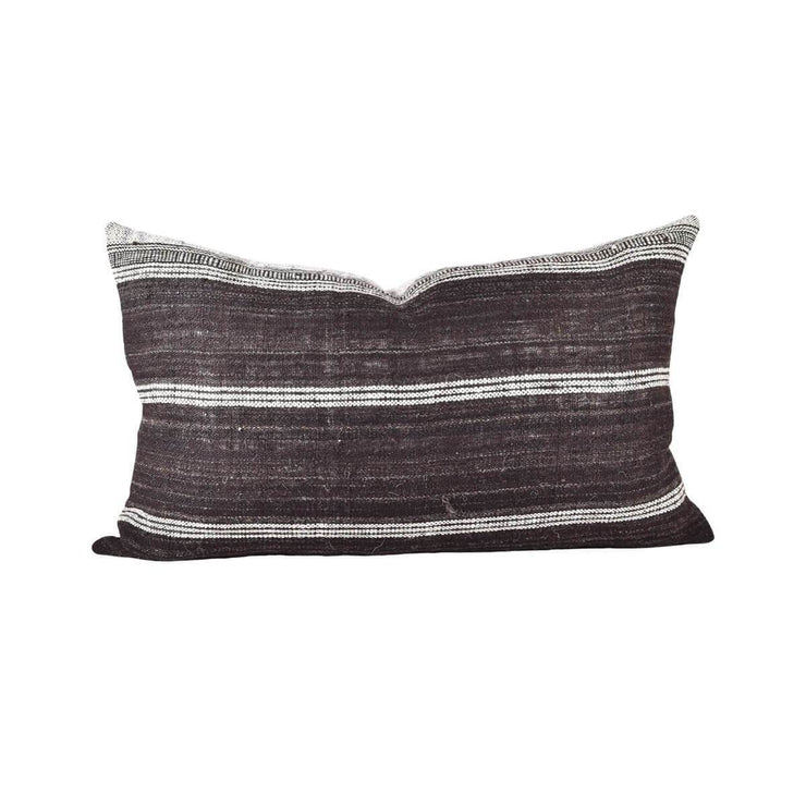Small, hand-woven wool lumbar pillow with brown and white stripes.