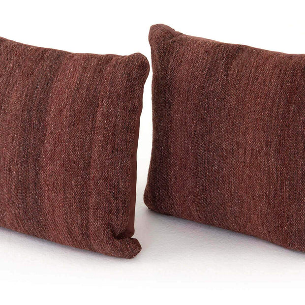 Closeup of the maroon colour variations and texture on the woven throw pillow.