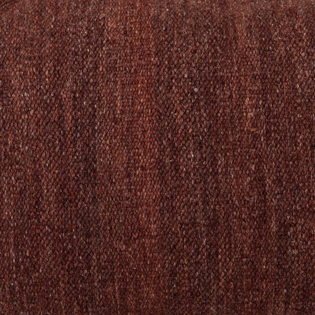 Texture details and closeup of the woven maroon decorative pillow.