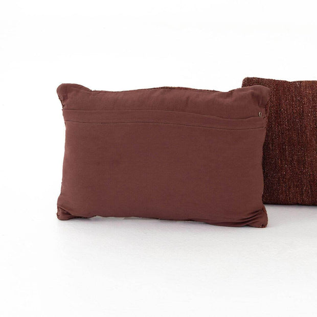 Maroon cotton back on the woven decorative pillow.