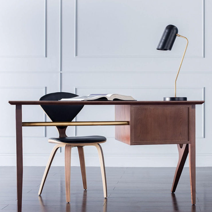 The contemporary black desk lamp with brass detailing in a modern office.