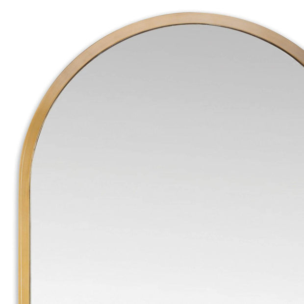 Modern rounded mirror with a stainless steel frame in a natural brass finish.
