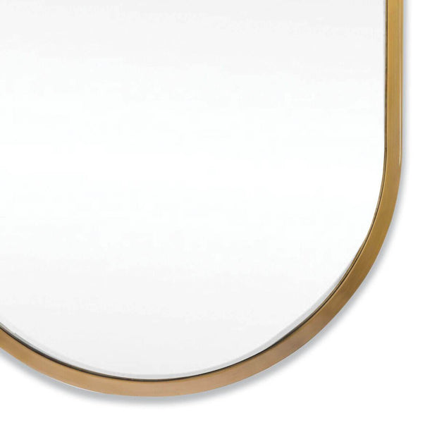Modern oval mirror with a thin natural brass frame.