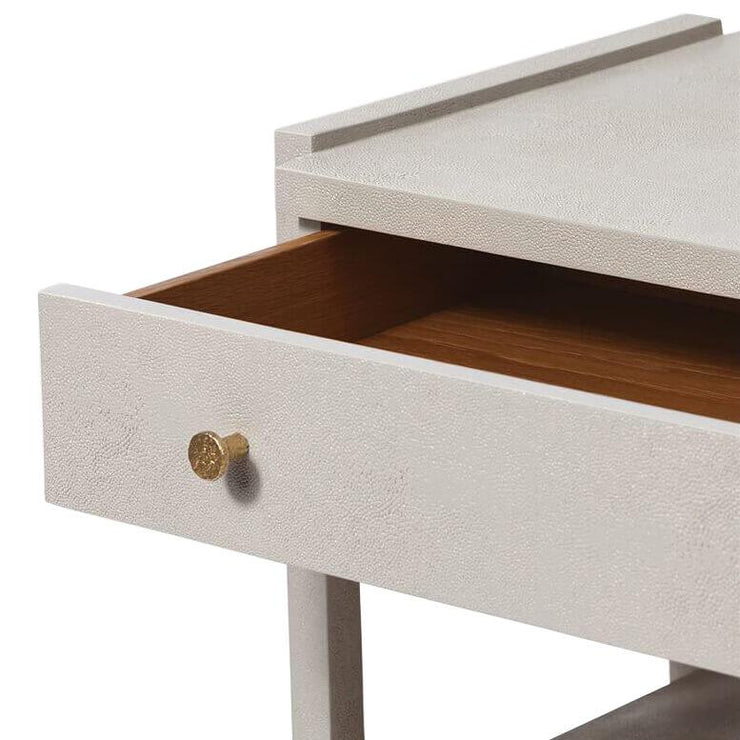 Closeup of the open drawer on the light grey vintage faux shagreen nightstand with simple gold knobs.