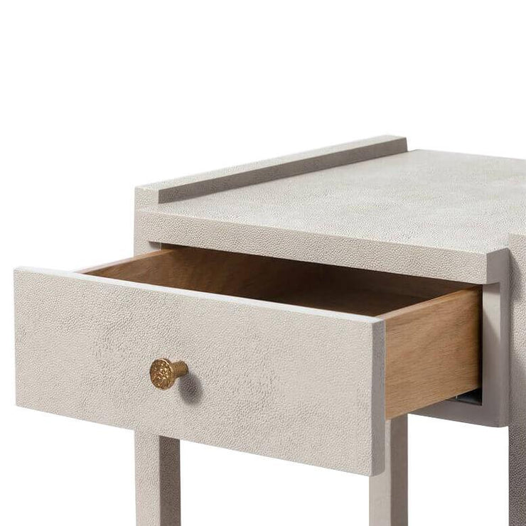Closeup of the light grey nightstand with two drawers and a simple gold knob.