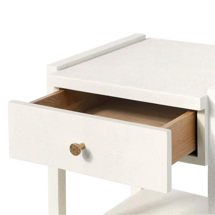 Closeup of the open drawer with a white faux shagreen finish and off-set drawers with a gold knob.