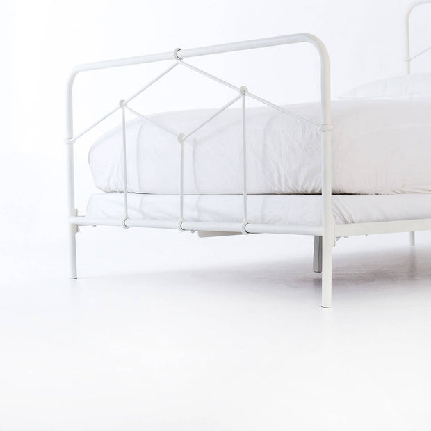 Closeup of the geometric bed made from white iron tubing.