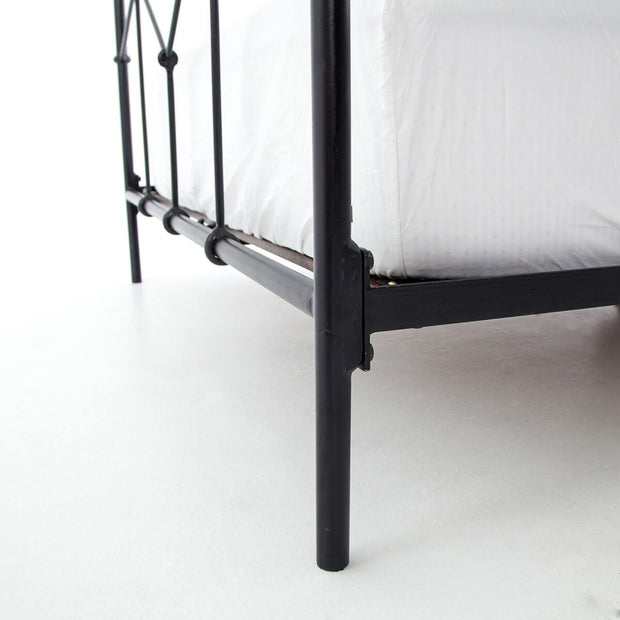 Closeup of the black iron tube legs and bedframe on the Stratford Bed.