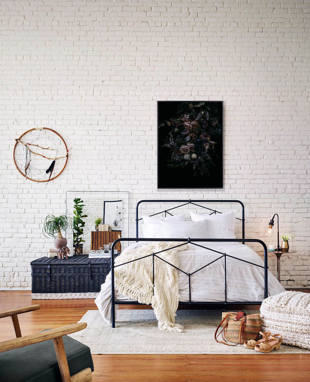 Simple black iron bed in a boho bedroom.