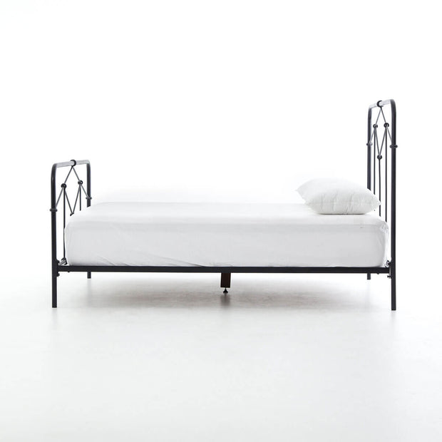 Side view of a simple iron bed with black, geometric patterns.