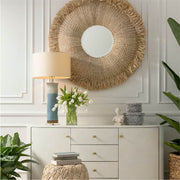 A large, statement circle mirror in a living room with a raffia frame and tufted details.