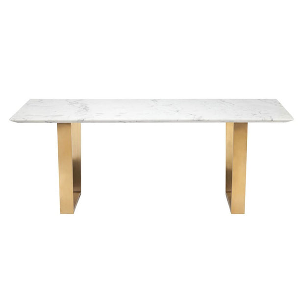 The Stelvio Dining Table has geometric stainless steel legs in a brushed gold finish and a rectangle texture marble top.