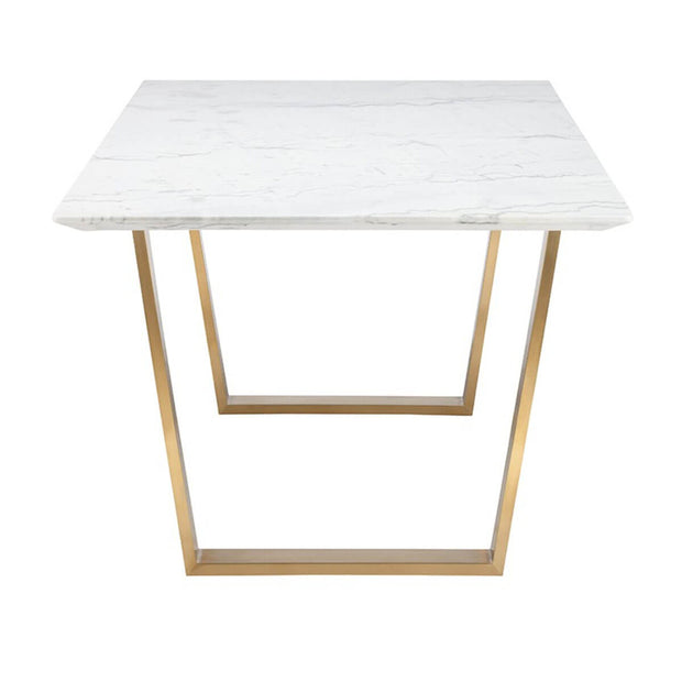 End view of the geometric gold legs and white marble tabletop on the modern dining room table.