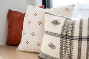 Neutral pillow with a dot inspired pattern in a collection of decorative pillows.