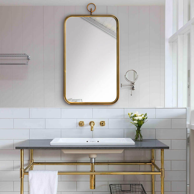 Small brass bathroom mirror over a sink.