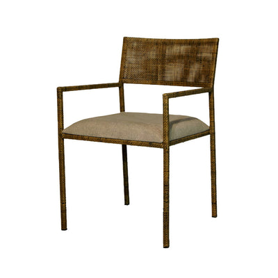Indoor dining arm chair with aged rattan material and grey linen upholstered seat cushion.