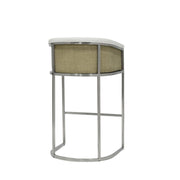 Modern bar stool with brushed stainless steal legs, upholstered seat and inside backrest, and cane matting detail.