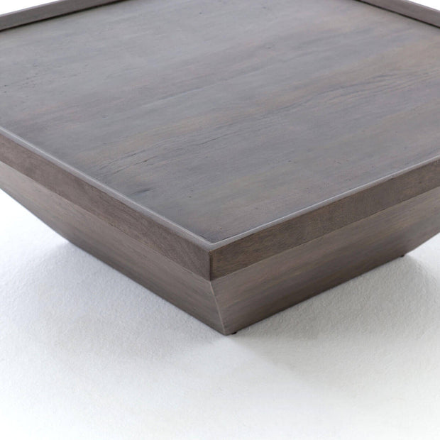 Square coffee table with recessed tabletop in a dark grey finished.