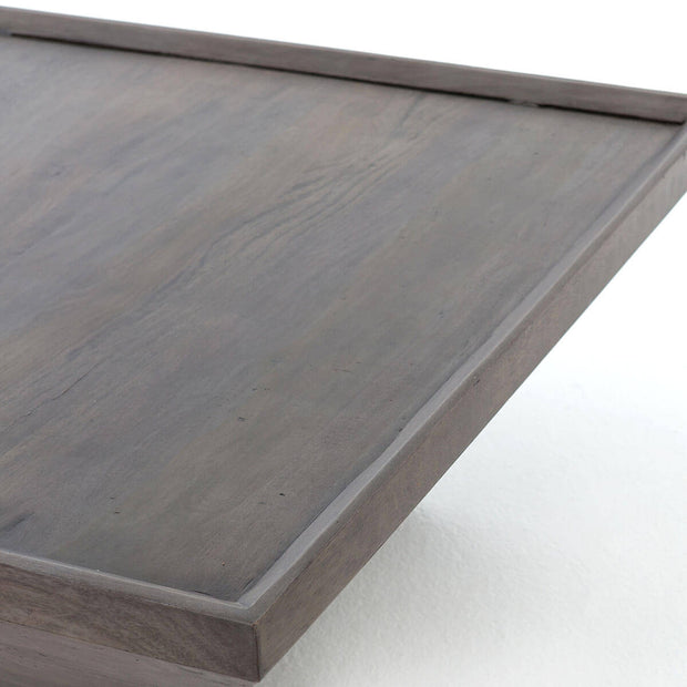 Recessed tabletop details on a dark grey, square coffee table.