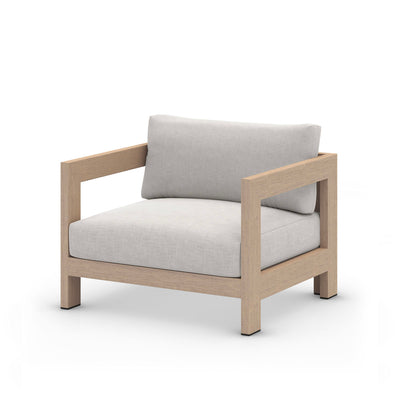 Outdoor lounge chair with light grey fabric upholstery and teak frame.