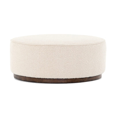 Large round upholstered white ottoman. Ottoman to be paired with a sectional in a living room.