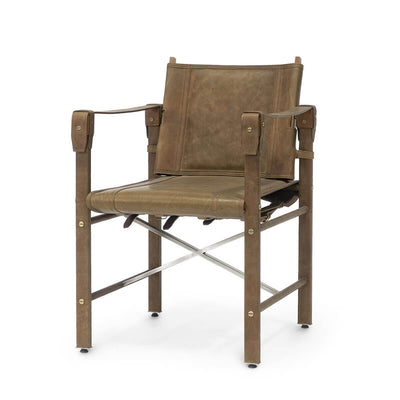 The Santiago Arm Chair has a stainless steel frame and legs that are wrapped in brown aniline leather with buckles and brass nailhead details.