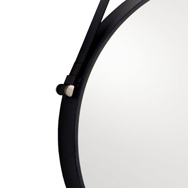 Black iron frame and leather hanging strap on a modern, circular mirror.