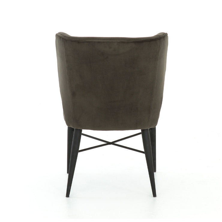 Back view of a dining chair with cone-shaped tapered black iron legs and suede upholstery.