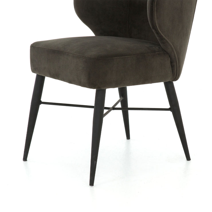 Close up view of indoor dining chair with cone-shaped tapered legs made of black iron.