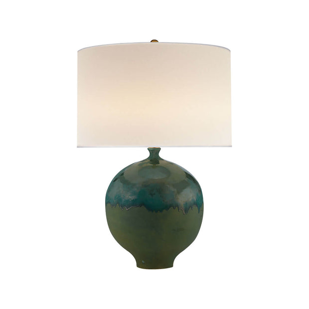 The Gaios Table Lamp has a rounded, textured volcanic verdi body and a round linen shade.