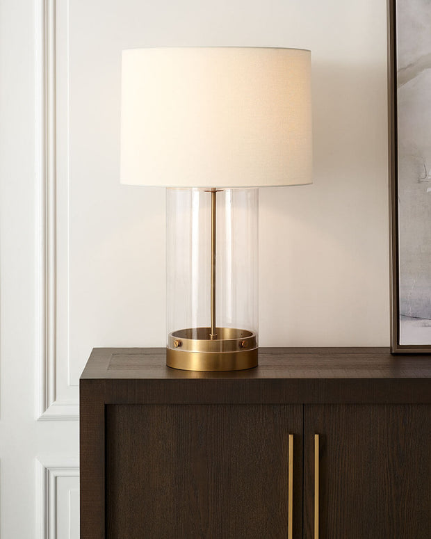 Modern glass table lamp with brass details on a living room side table.