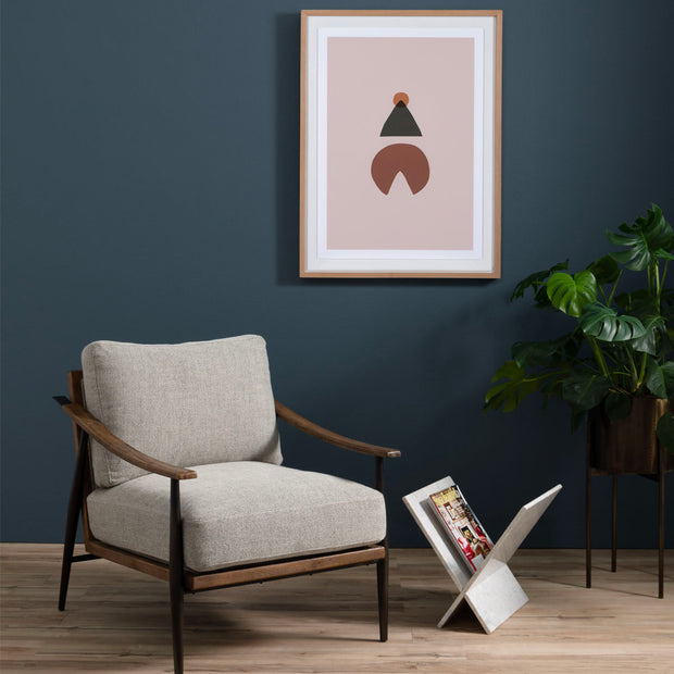 Light grey chair with wood frame in a lounge area next to some artwork, greenery, and a magazine stand.