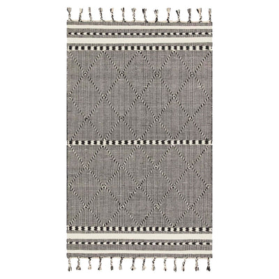 A hand loomed textural rug with fringed edges in a geometric black and white patter.
