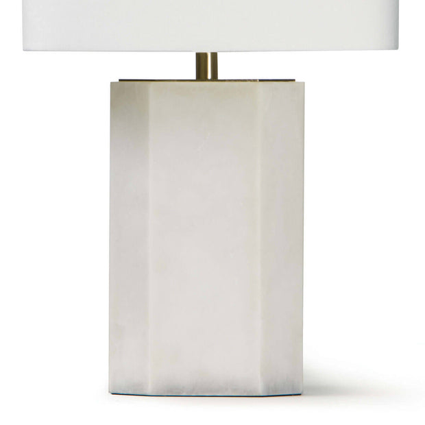 Geometric stone base on a modern table lamp with brass details and a natural linen shade.