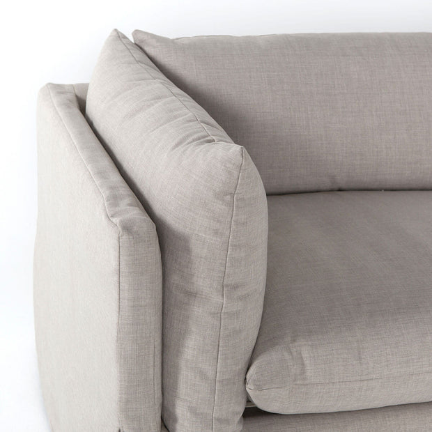 Slip covered, neutral pillows on a large sectional.
