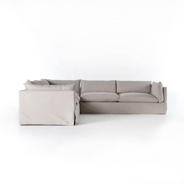 Side view of a modern fabric sectional with a neutral slipcover, high shelter arms and pillow-like cushions.