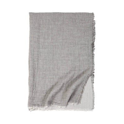 The Trento Oversized Throw is a light grey and cream stonewashed cotton and linen throw with frayed edges and a soft gauzy weave.