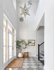 Hillside artwork in a grand entranceway with Moroccan-style lanterns. and checkered floors.