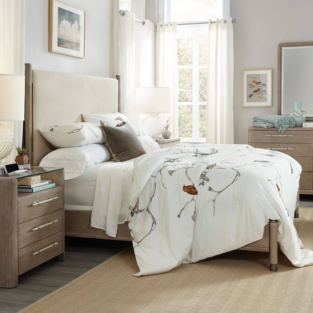 Wood and linen upholstered bed frame in a coastal inspired bedroom.