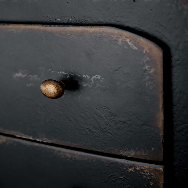 Close up of the burnished brass hardware and distressed wood on the heirloom nightstand.
