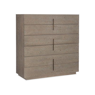The Vence Chest is made of solid oak with a grey, flaky oak finish and has six drawers with antique gold, textured drawer pulls.