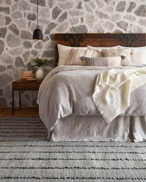 Dakota Charcoal Rug in a bedroom. Dark neutral textured bedroom rug.