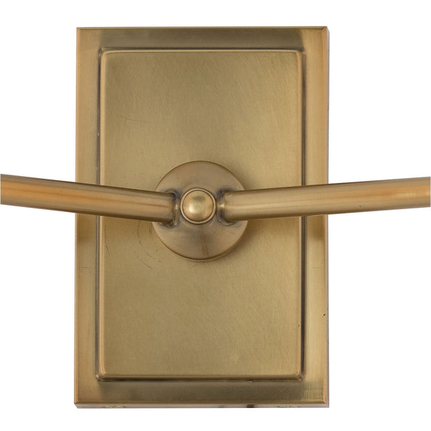 Antique brass backplate and details on a modern living room wall sconce.