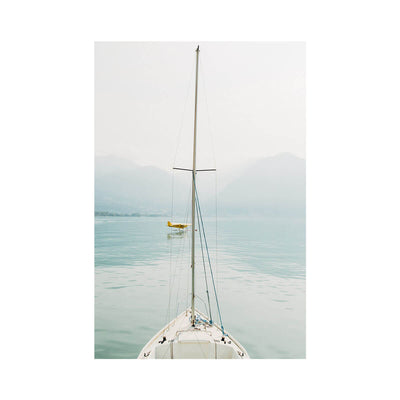 Italy is a soft nautical photograph of a sailboat in a calm lake by artist Brendan Burden.
