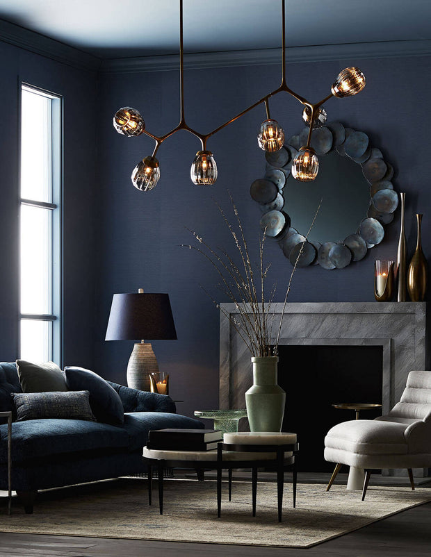 Round, statement coffee table in a moody living room.
