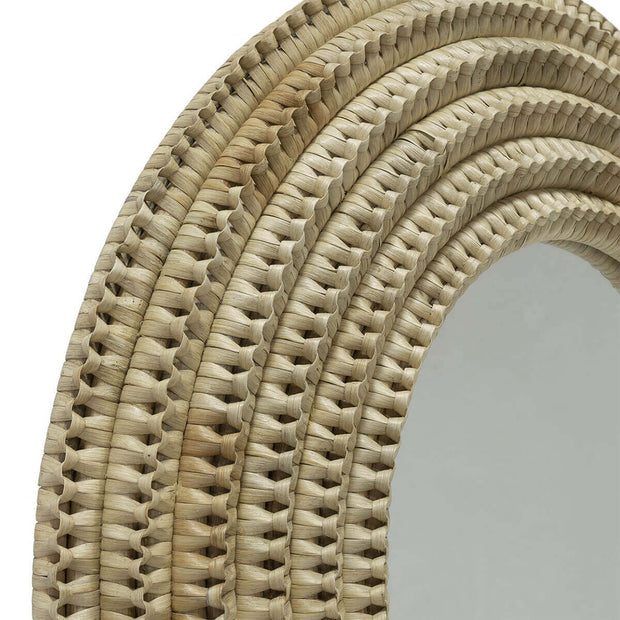 Organic circular hallway mirror with woven rattan details.
