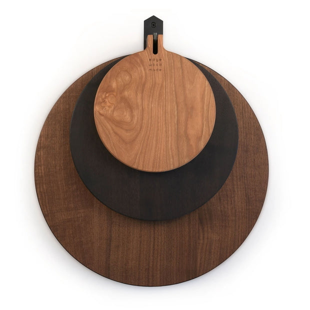 Round cutting boards in varying sizes made from walnut wood.