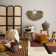 Teak stool styled with layers of pillows, rugs, and accessories.