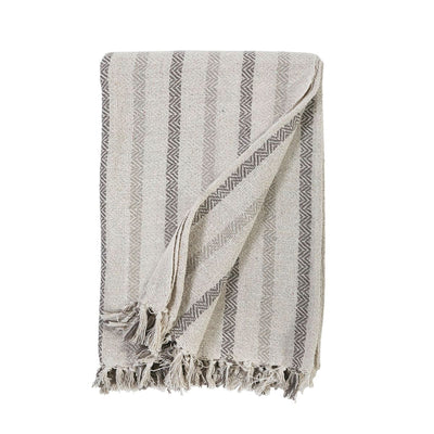 The Lewiston Oversized Throw is made of 100% cotton that forms a soft striped pattern with herringbone details and small tassels on the top and bottom edges.